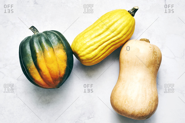 Three squash on white surface viewed from above