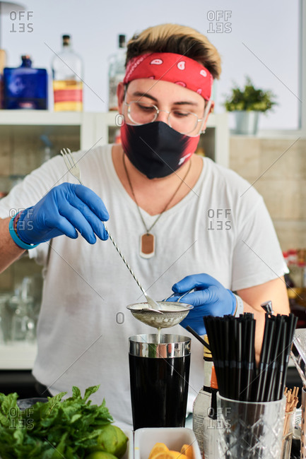 Male barkeeper in mask and gloves pouring milk into shaker while preparing delicious smoothie in cafe