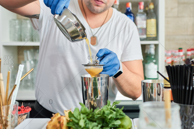 Anonymous crop male barkeeper in gloves pouring milk into shaker while preparing delicious smoothie in cafe