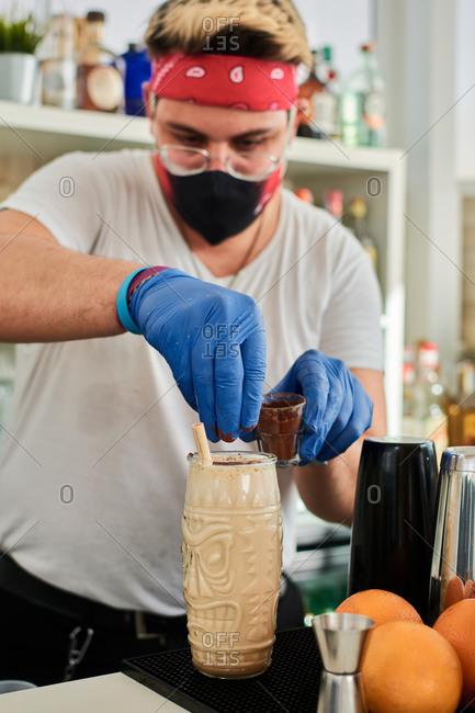 Informal male bartender in protective mask and headband preparing milkshake in glass at counter