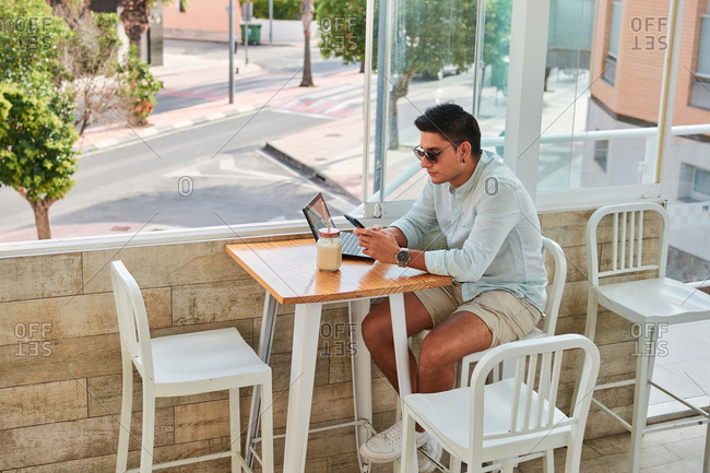 Side view of young stylish male freelancer using smartphone while working remotely on laptop in cafe