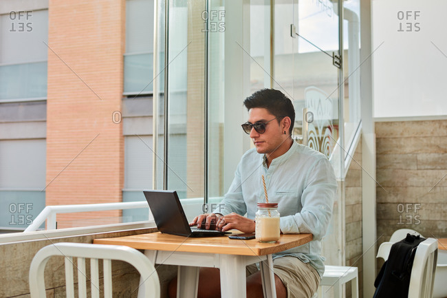 Young stylish male freelancer working remotely on laptop in cafe