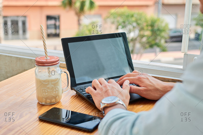 Crop faceless young male freelancer typing on laptop while working remotely in cafe sitting at table with smartphone and beverage