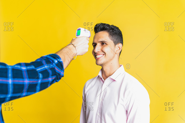 Crop unrecognizable male measuring temperature of happy colleague using digital thermometer on yellow background
