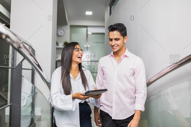 Cheerful young entrepreneurs in trendy apparel interacting while watching tablet on stairs at work
