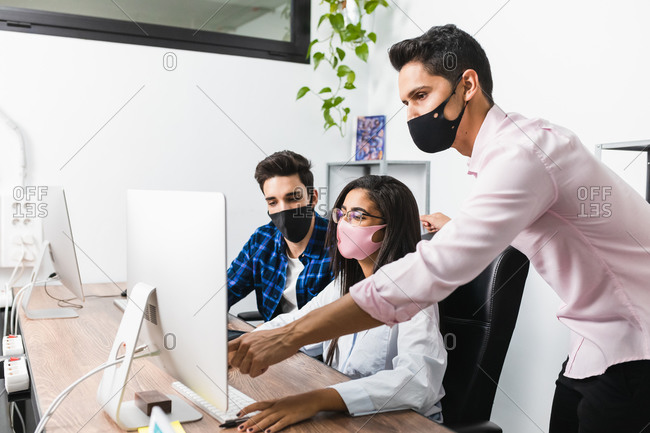 Anonymous entrepreneur in mask showing project on desktop computer while interacting with young coworkers in office