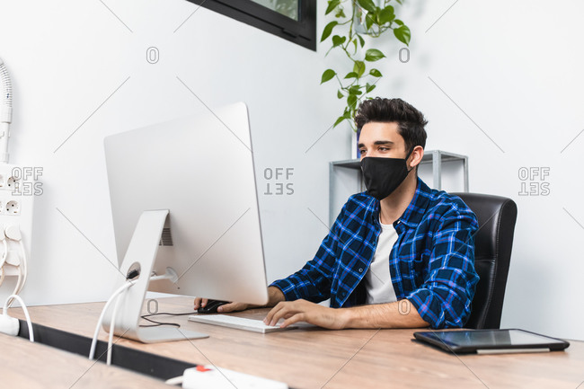 Unrecognizable young stylish male entrepreneur in face mask working on desktop computer in modern workspace