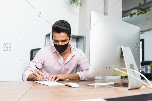 Anonymous concentrated businessman in mask taking note on paper near desktop computer while working on project
