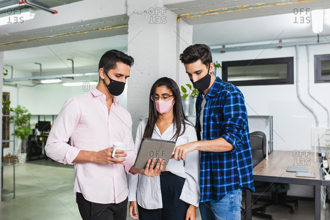 Group of unrecognizable entrepreneurs in masks and stylish outfit sharing tablet while working on project at work