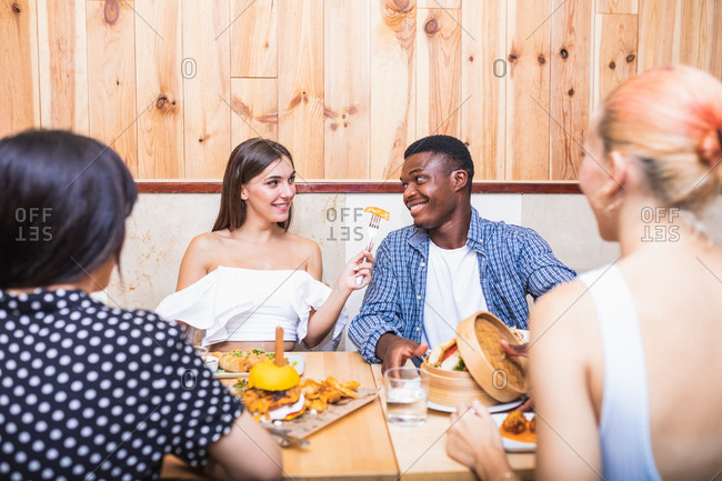 Positive young multiracial friends eating tasty dishes and burgers while gathering in modern restaurant