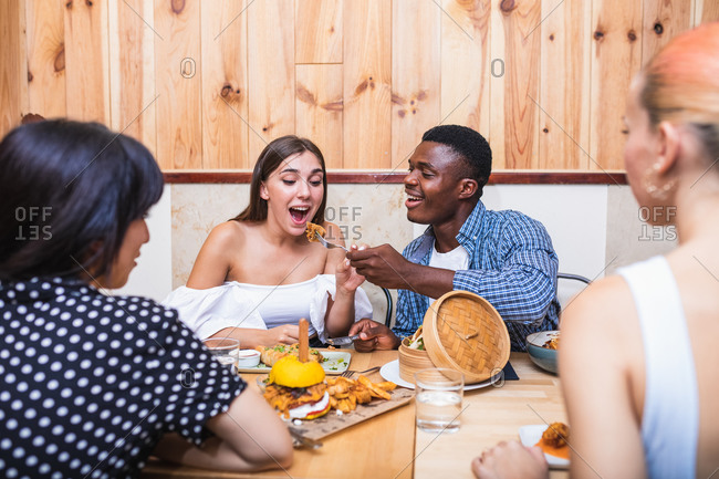 Excited multiracial friends wearing stylish outfits gathering at table in restaurant and spoon feeding each other with tasty fresh dishes