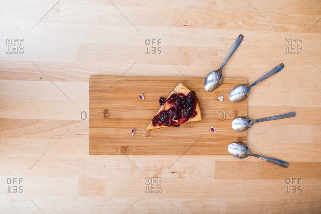 Top view composition of yummy homemade cherry pie slice placed on wooden board with teaspoons