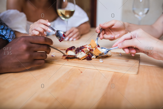 Crop anonymous multiethnic friends enjoying tasty cherry pie while gathering together for dinner in restaurant