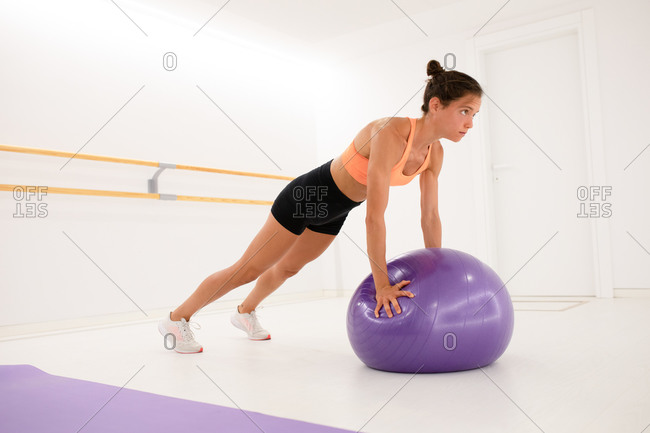 Side view of young fit focused athlete in sports clothes using fitness ball during training on floor and looking away