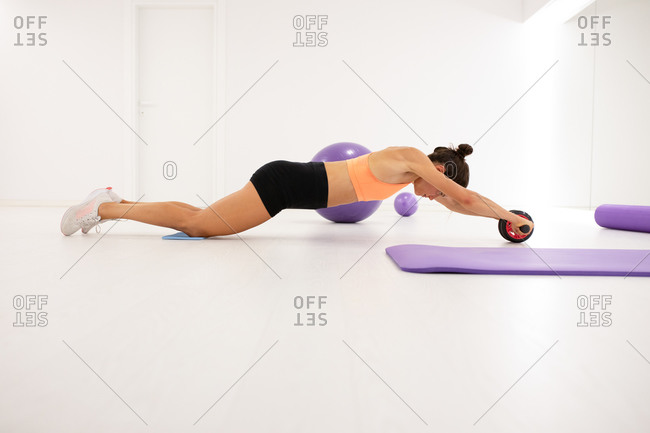 Side view of slender female athlete in sports clothes working out with roller wheel on floor near mat