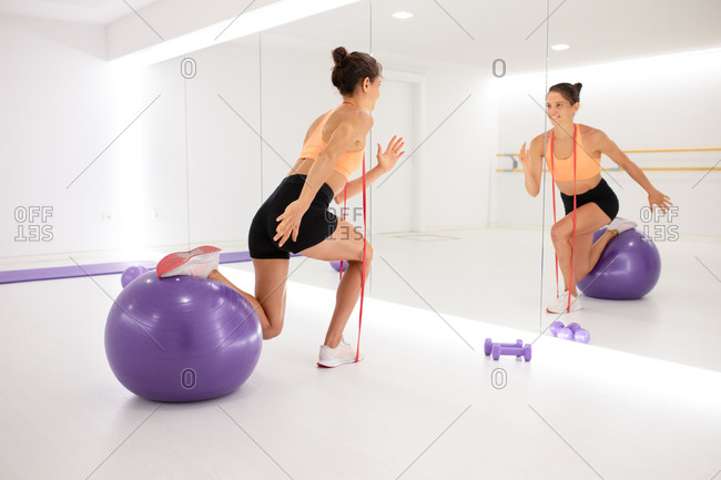 Back view of young fit content female athlete warming up on exercise ball near mirror and dumbbells in gym