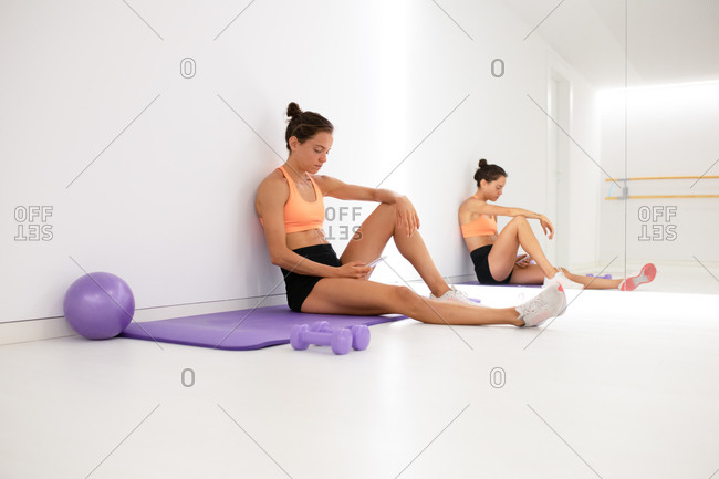 Female athlete in face mask and sportswear chatting on cellphone while having break from workout and reflecting in mirror in gymnasium