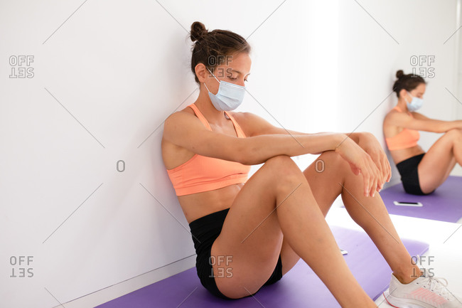 Exhausted female athlete in sports clothes and face protection mask sitting with closed eyes on mat near wall and mirror after exercising in gymnasium