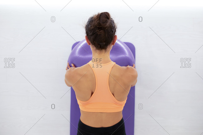 From above back view of anonymous female athlete in sports clothes working out with exercise ball on mat in gymnasium