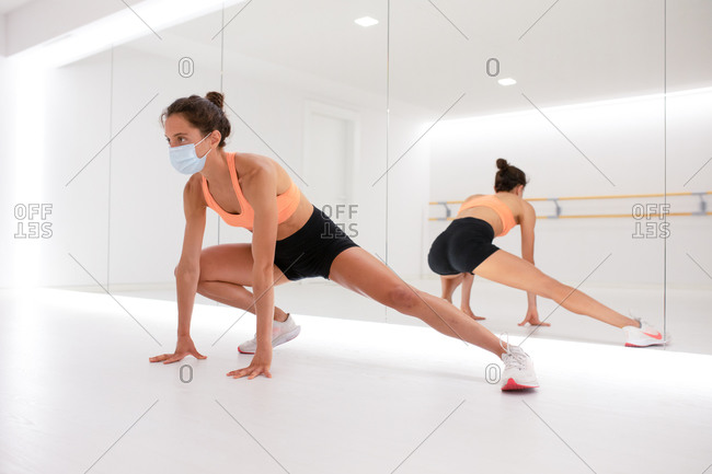 Unrecognizable slim female athlete in sports clothes and face mask exercising on floor while reflecting in mirror and looking away in gym
