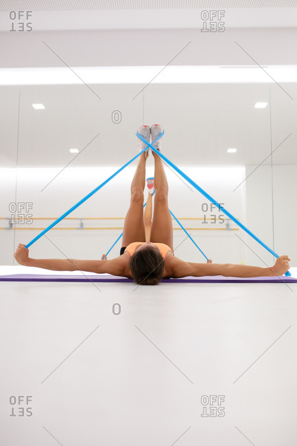 Fit anonymous female athlete stretching arms and legs with elastic tape while lying on mat and reflecting in mirror
