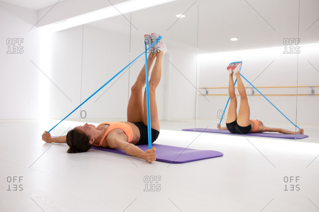 Fit female athlete stretching arms and legs with elastic tape while lying on mat and reflecting in mirror