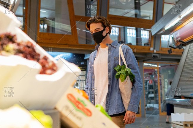 From below young male customer in protective mask carrying eco friendly recycled fabric shopping bag and choosing fresh groceries while buying food in supermarket
