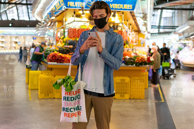 Young male buyer in protective mask holding reusable cotton bag with groceries and browsing smartphone during shopping in grocery market