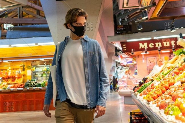 Young male customer in protective mask carrying eco friendly recycled fabric shopping bag and choosing fresh groceries while buying food in supermarket