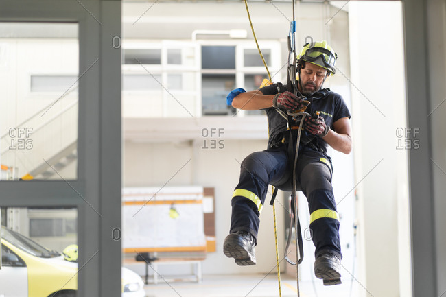 Young fireman in protective hardhat and gloves ascending wall on colorful rope during routine practices