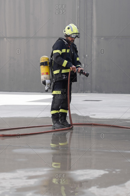 Anonymous firefighter in uniform and protective helmet standing with fire extinguisher and rubber hose on pavement during routine practices