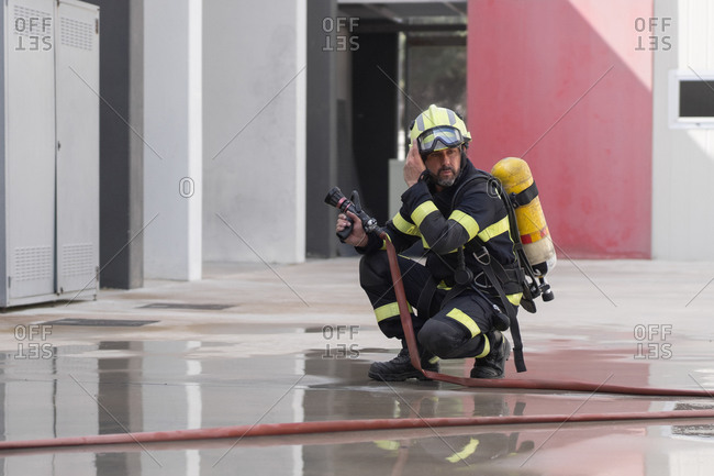 Contemplative unshaven firefighter in uniform with stripes and protective helmet reflecting in cement surface near hose at work while looking away