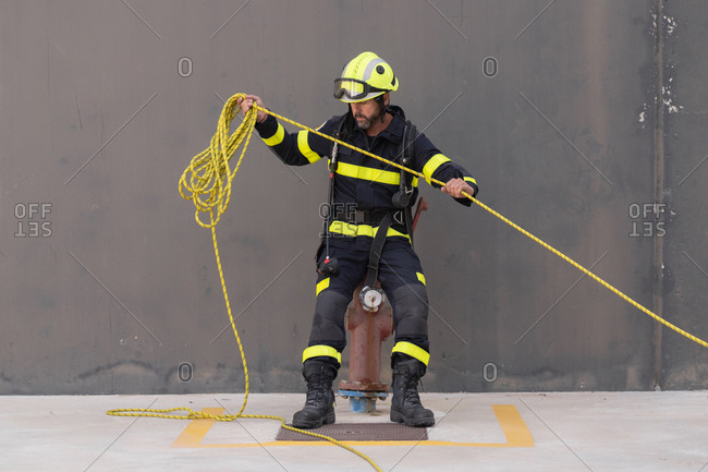 Bearded firefighter in protective hardhat and bright uniform standing on cement floor with rope during routine practices at work