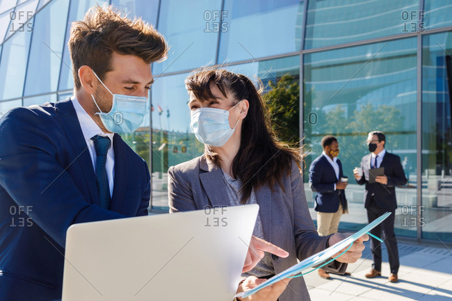 Unrecognizable young man and woman in formal suits and medical masks examining documents while working together on street using laptop near modern business building