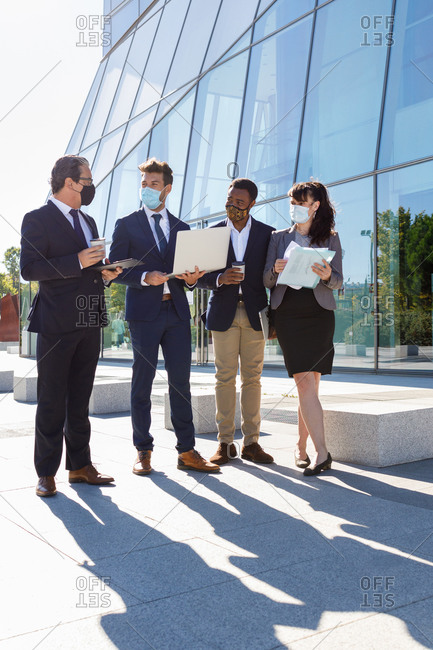 Full body of anonymous diverse coworkers working on laptop in formal suit and medical mask using laptop while standing on street