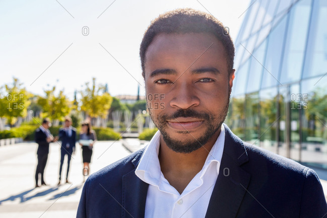 Happy young unshaven African American male entrepreneur in classy suit standing on street neat contemporary business building and looking at camera