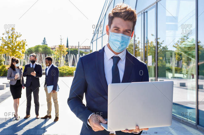 Unrecognizable young male manager in stylish suite and protective mask working on laptop while standing on street near building and diverse colleagues