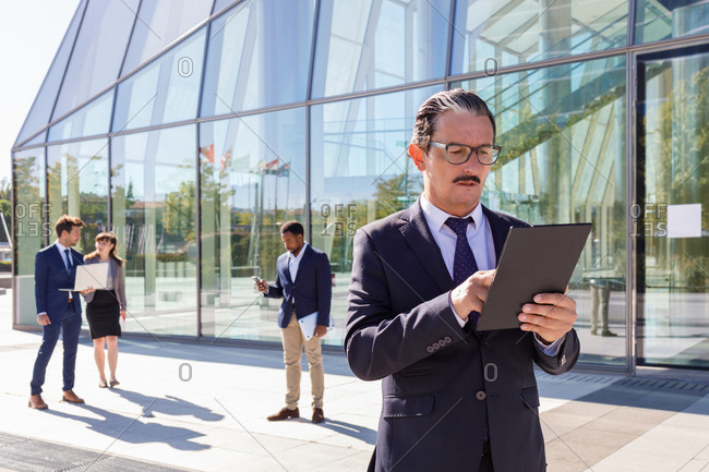 Serious middle aged male manager with mustache in classy outfit holding tablet in hand while thinking about business strategy on street