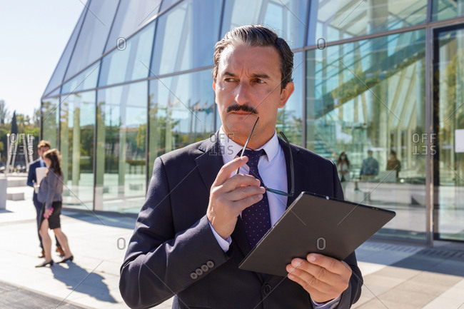 Serious middle aged male manager with mustache in classy outfit holding documents in hand and looking away while thinking about business strategy on street