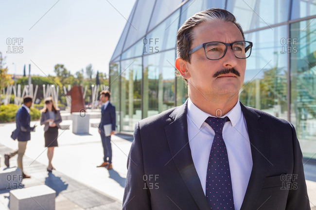 Serious middle aged male manager with mustache in classy outfit looking away while thinking about business strategy on street