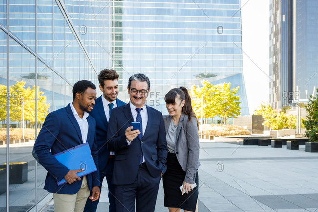 Group of happy multiracial colleagues in classic suites laughing while reading good news on smartphone standing together on street