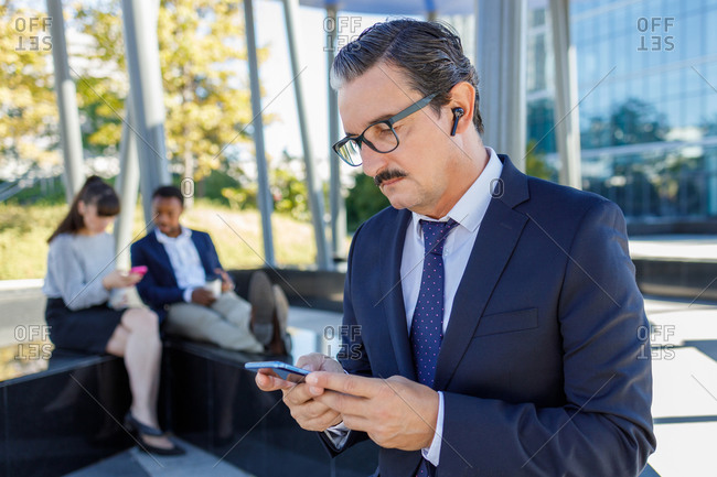 Positive respectable adult businessman in elegant suit and eyeglasses smiling while browsing smartphone on street near modern skyscrapers