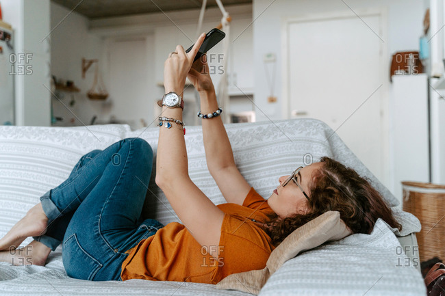 Side view of young barefooted lady with curly ginger hair in casual outfit lying on comfortable sofa and taking selfie on smartphone at home