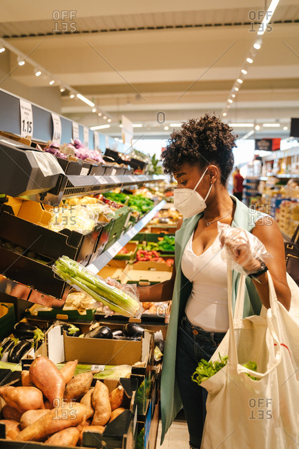 Side view of young African American female in protective mask and gloves choosing red apples while visiting grocery store during coronavirus pandemic