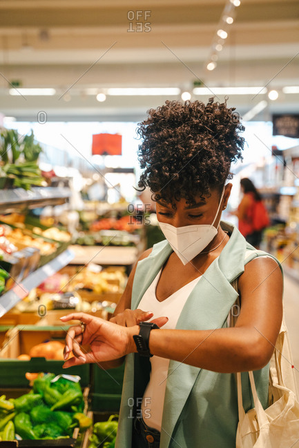 Modern African American female buyer in protective mask for coronavirus prevention using smart watch  while standing near stall with grocery products in supermarket