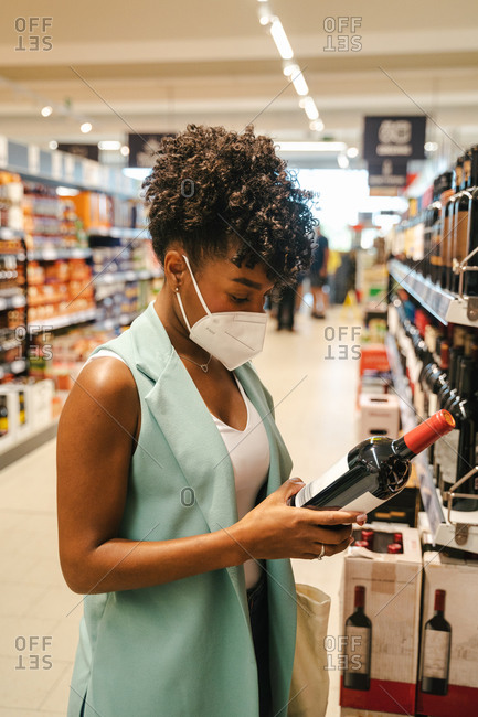 Side view of crop African American female customer in protective mask for coronavirus prevention examining bottle of wine while choosing drinks in supermarket