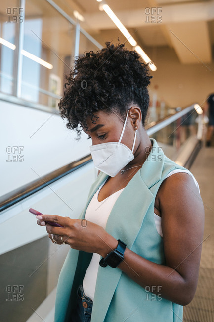 Side view of positive young African American female in casual outfit and protective mask using mobile phone while standing inside public building with escalator