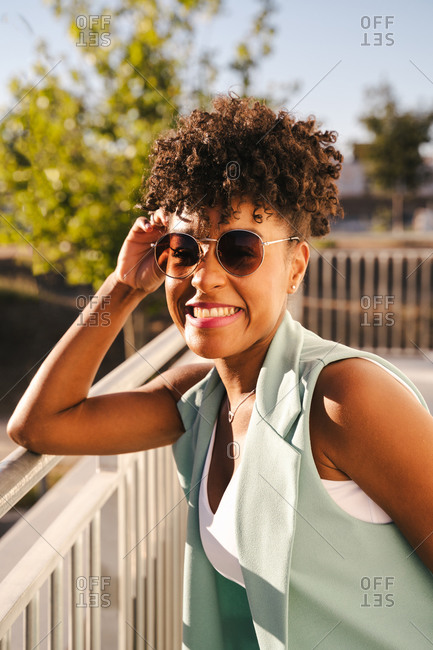 Joyful young African American female with Afro hairdo and trendy sunglasses leaning elbow on railing and looking at camera while enjoying sunny summer day in park