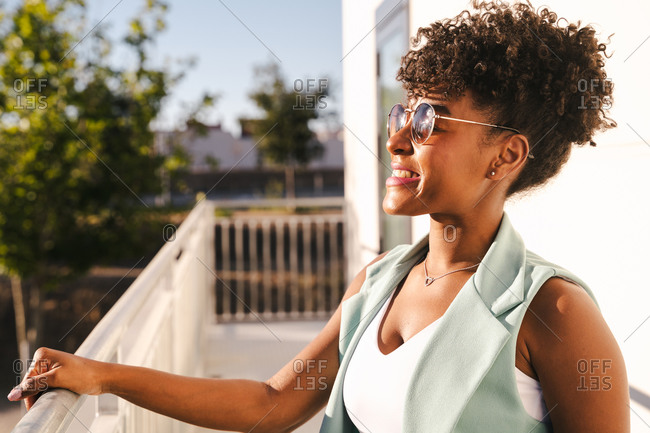 Joyful young African American female with Afro hairdo and trendy sunglasses leaning elbow on railing and looking away while enjoying sunny summer day in park