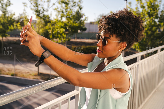 Joyful young African American female with Afro hairdo and trendy sunglasses taking a selfie while enjoying sunny summer day in park